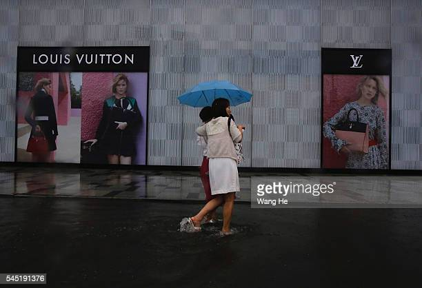 Two women walk on a flooded street in front of Louis Vuitton> on July 6 2016 in Wuhan China