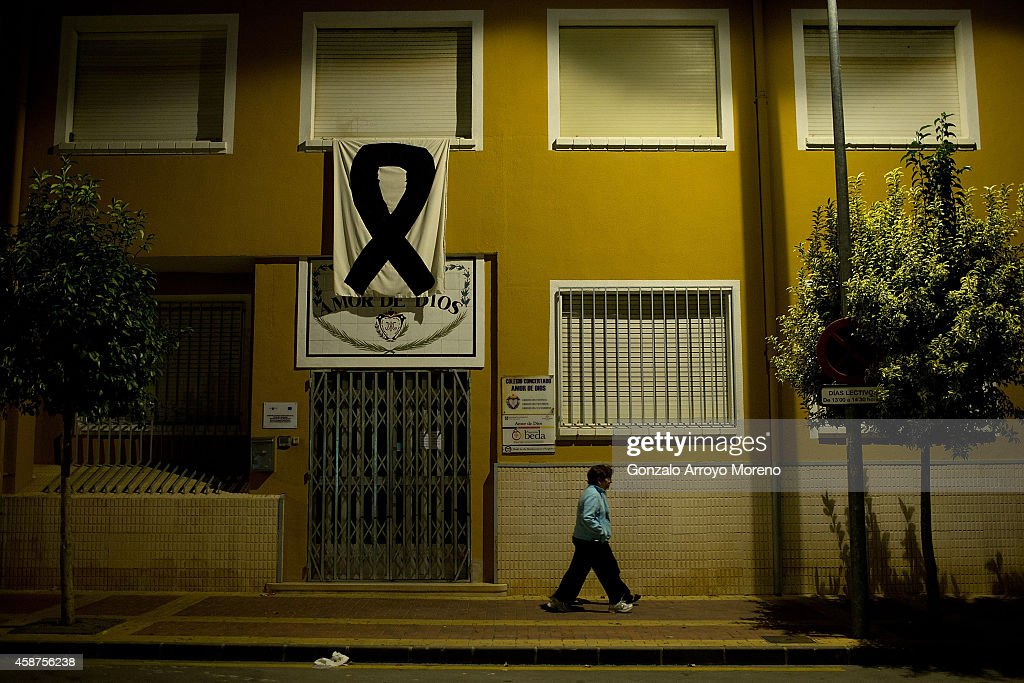Two women walk on at one of Bulla,s primary schools with a black bow sign unfolded in memory of the 14 victims who were killed after their bus fell 15 meters on November 10, 2014 in Bullas, at Murcia province, Spain. Schools and other establishments have remained close today in the memory of victims. Fourteen people were killed and 42 injured after their bus fell 15 meters from Calasparra road. The travellers were returning from Madrid to the Murcian town of Bullas after attending a religious ceremony at the Convent of the Barefoot Carmelites.