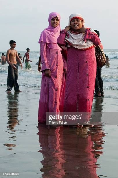 COX'S BAZAR BANGLADESH Two women walk on Cox's Bazar beach
