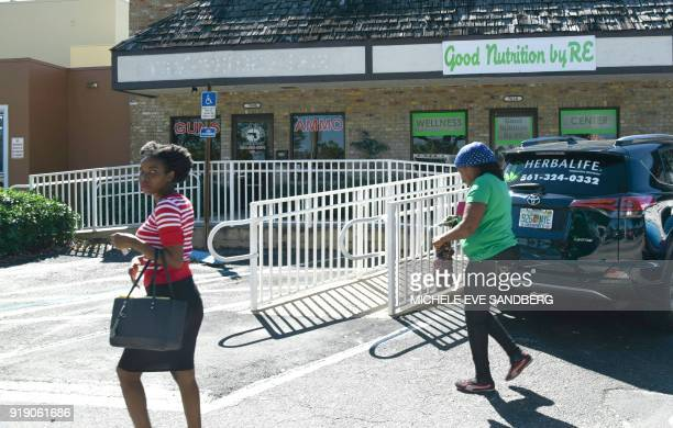 Two women walk outside of Sunrise Tactical Supply store in Coral Springs Florida on February 16 2018 where school shooter Nikolas Cruz bought his...