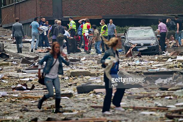 Two women walk over debris while rescue workers in the background interact with people near an explosion site in Oslo after two bombs rocked the...