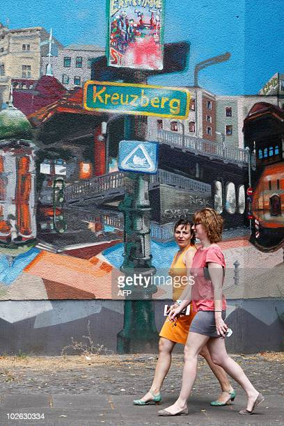 Two women walk past a building with a street scene painted on the wall in Berlin's Kreuzberg district on July 5 2010 AFP PHOTO / DAVID GANNON