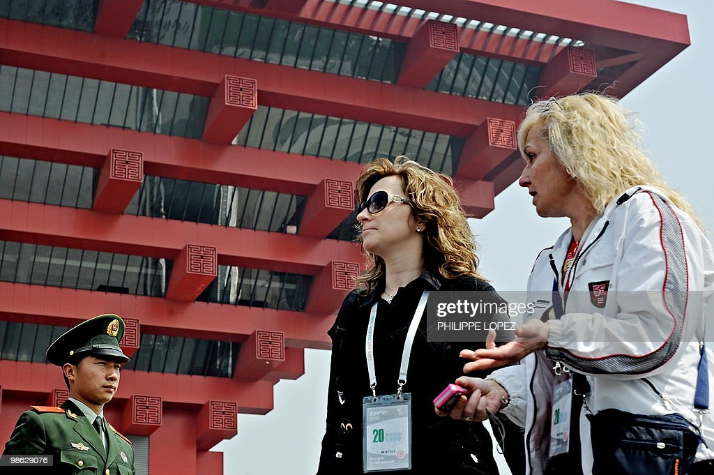 Two women walk past a Chinese soldier standing guard in front of the Chinese pavilion at the site of the World Expo 2010 in Shanghai on April 23, 2010. Expo organisers gave members of the public a preview of the largest-ever World's Fair as they tested facilities and public transportation before the official start on May 1.