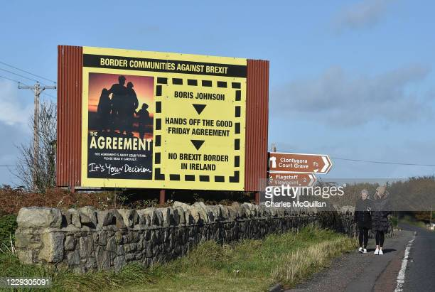 Two women walk past a fresh anti-Brexit billboard as they cross the border between Ireland and the United Kingdom on October 27, 2020 in Newry,...