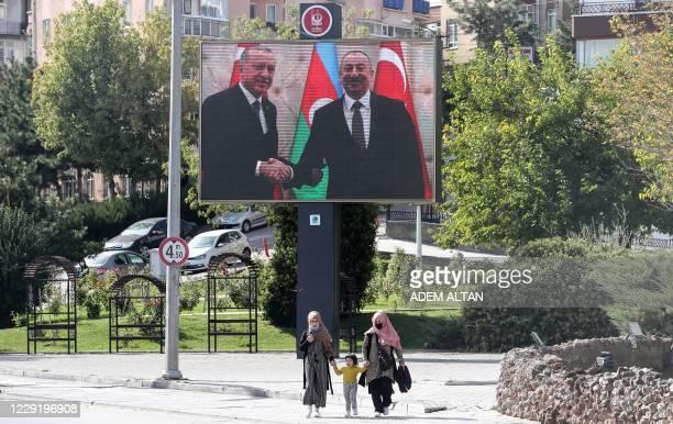 Two women walk past a large image of Turkish President Recep Tayyip Erdogan and Azerbaijani President Ilham Aliyev shaking hands displayed on a huge...
