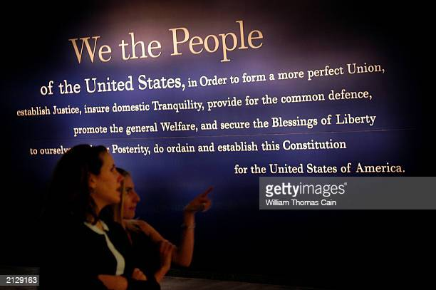 Two women walk past a painting of the beginning of the US Constitution during a preview of the National Constitution Center July 1 2003 in...
