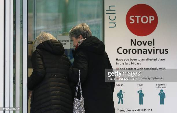 Two women walk past a sign providing guidance information about novel coronavirus at one of the entrances to University College Hospital in London on...