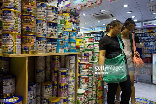 Two women walk past cans of baby formula displayed in a pharmacy in the Mong Kok area of Hong Kong China on Tuesday Oct 1 2013 China's 'Golden Week'...