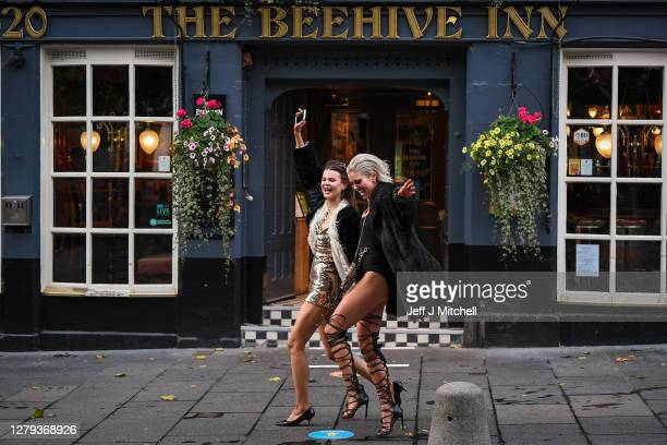 Two women walk past The Beehive pub in the Grassmarket following pubs closing at 6pm on October 9, 2020 in Edinburgh, Scotland. Pubs and restaurants...