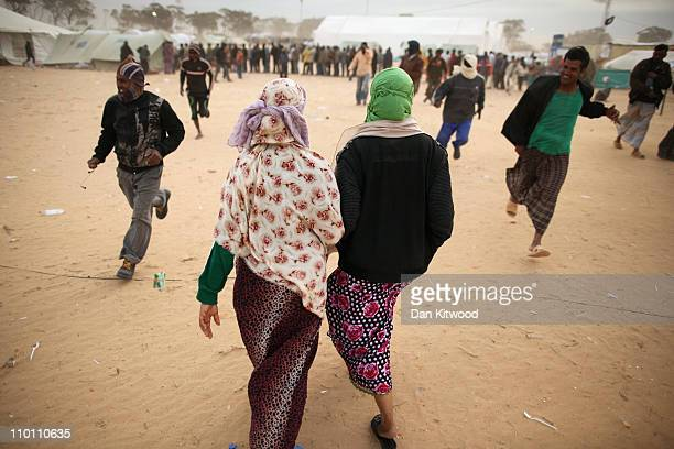 Two women walk through a United Nations displacement camp during a huge sandstorm on March 15 2011 in Ras Jdir Tunisia As fighting continues in and...