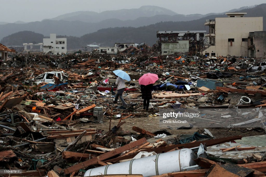 Two women walk through the rubble and devastation on March 20, 2011 in Rikuzentakata, Japan. Many people have begun to return to their homes as the search continues for thousands still missing after a 9.0 magnitude strong earthquake struck on March 11 off the coast of north-eastern Japan. The quake triggered a tsunami wave of up to 10 metres which engulfed large parts of north-eastern Japan.