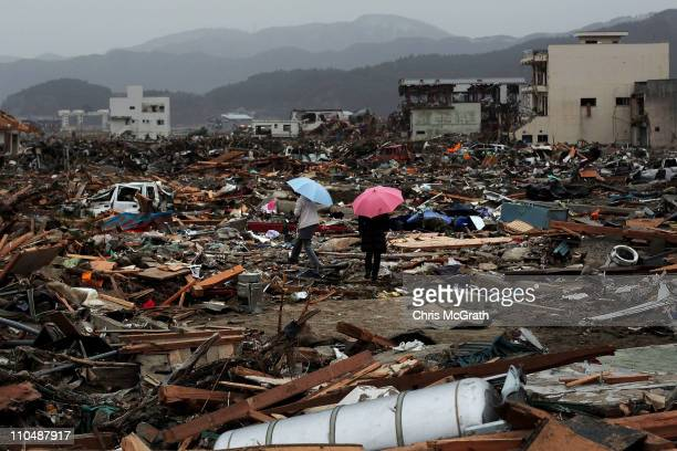 Two women walk through the rubble and devastation on March 20 2011 in Rikuzentakata Japan Many people have begun to return to their homes as the...