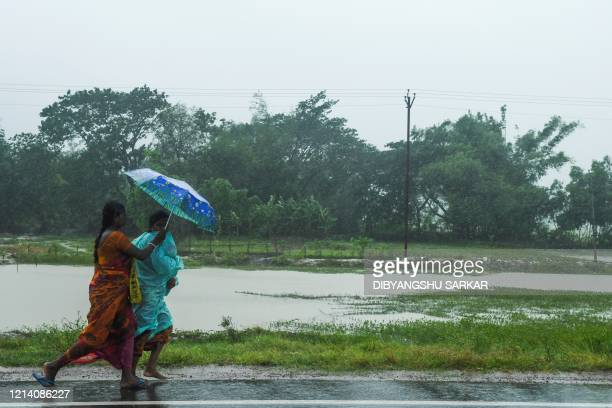 TOPSHOT Two women walk with an umbrella under the rain ahead of the expected landfall of cyclone Amphan in Midnapore West Bengal on May 20 2020 India...