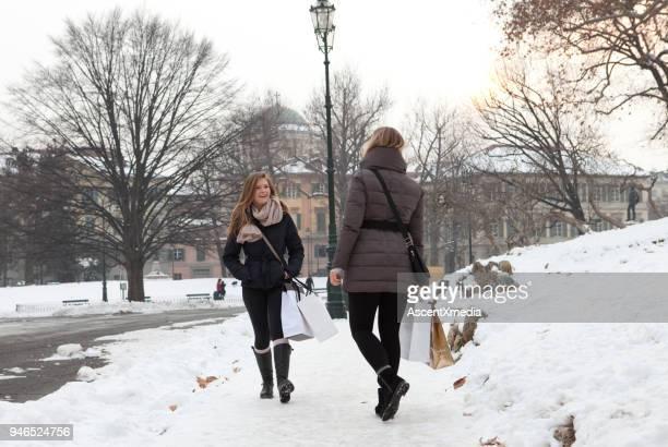 2 人の女性がショッピング バッグ、雪に覆われた公園、トリノ、ピエモンテ、イタリアで歩く - イタリア ピエモンテ州 ストックフォトと画像