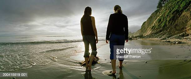 two women walking along beach, rear view - rolled up trousers stock pictures, royalty-free photos & images