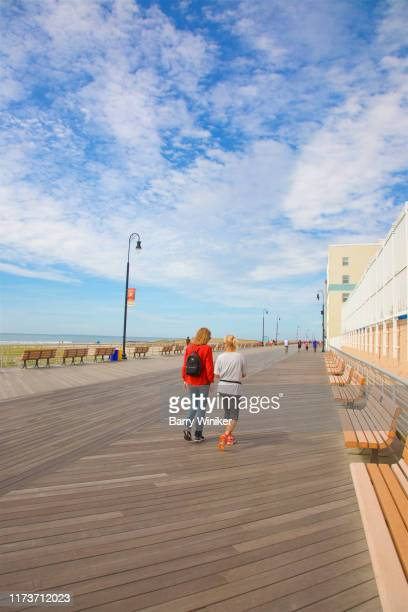 two women walking and enjoying the new boardwalk in long beach, new york - barry wood stock pictures, royalty-free photos & images