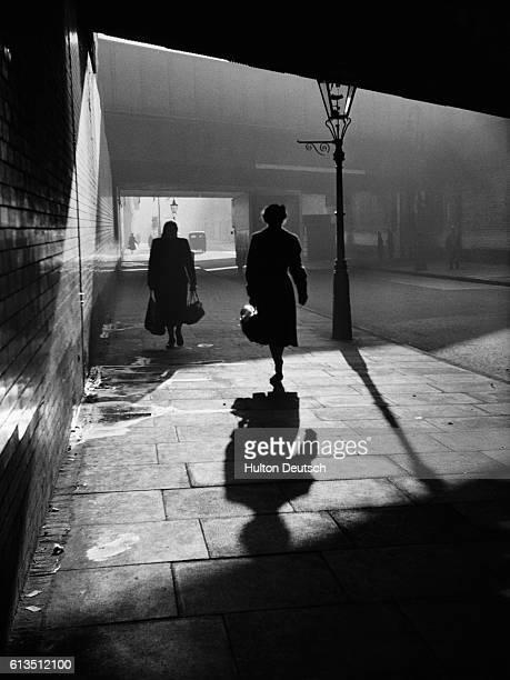Two women walking down a dark street in London