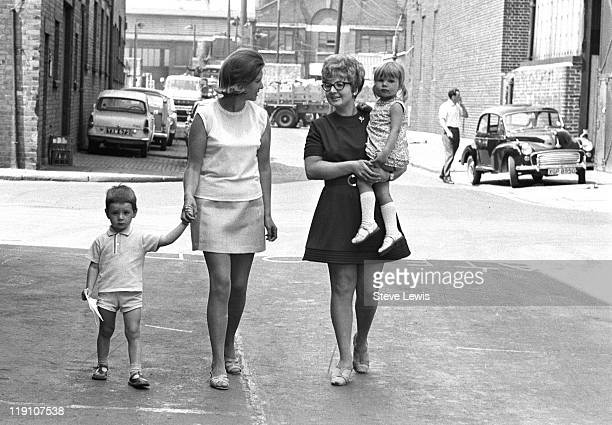 Two women walking down a street with a boy and a girl east London circa 1970