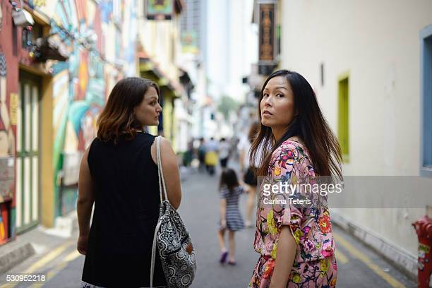 Two women walking down Singapore's colourful Haji Lane