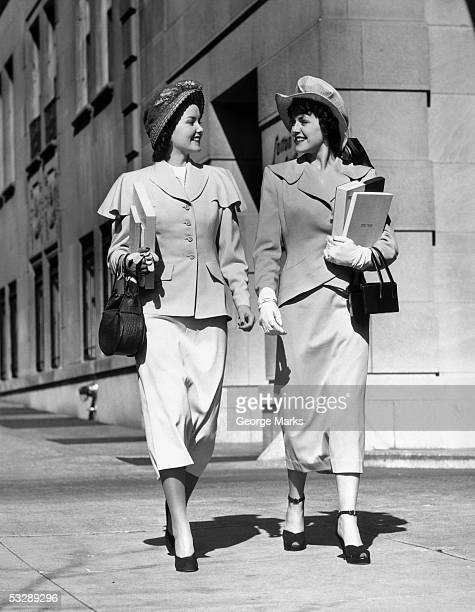 two women walking down the street - fashions hats and handbags stock pictures, royalty-free photos & images