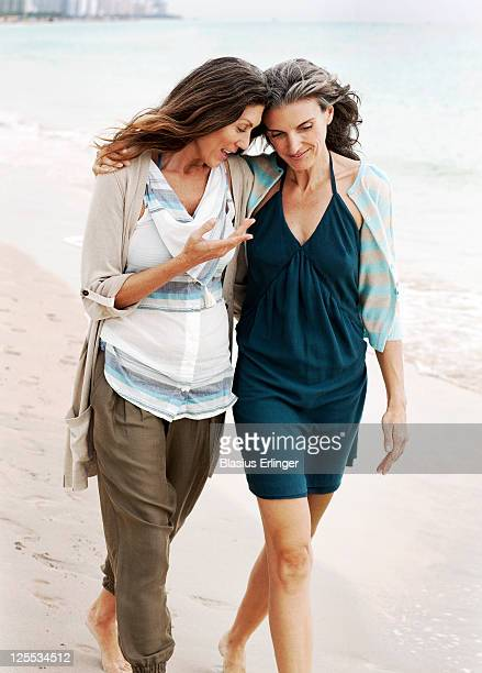 two women walking on beach - female friendship stock pictures, royalty-free photos & images