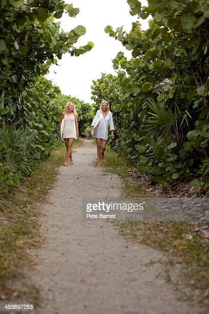 Two women walking on path with surfboards