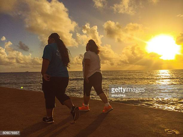 two women walking on the beach at sunset, hawaii, usa - fat woman at beach stock photos and pictures