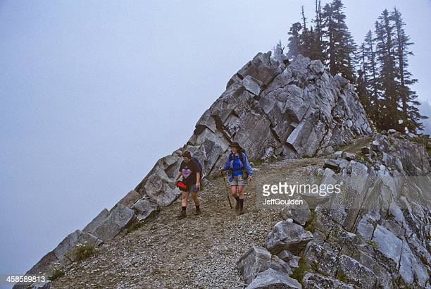 two hikers walk the pacific crest trail in fog - pacific crest trail stock pictures, royalty-free photos & images