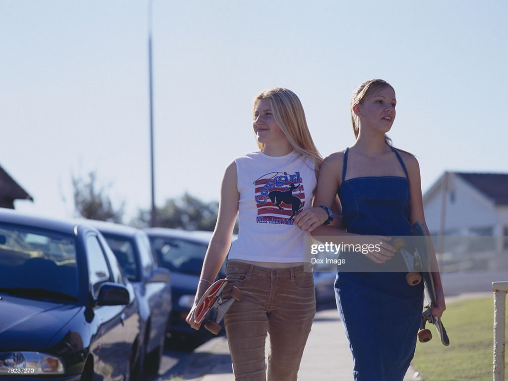 Two women walking on walkway holding skateboards : Stock Photo