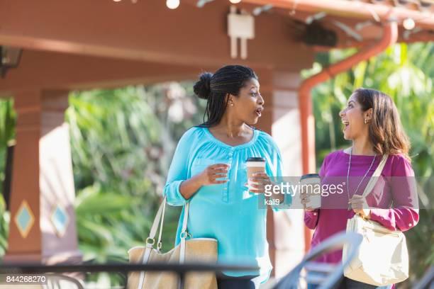 Two women walking outdoors, talking, drinking coffee