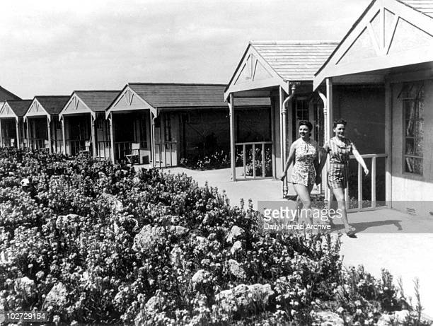 Two women walking past chalets at a Butlins holiday camp 8 July 1939 'At an inclusive 60 or 70 shillings a week according to the season you live...