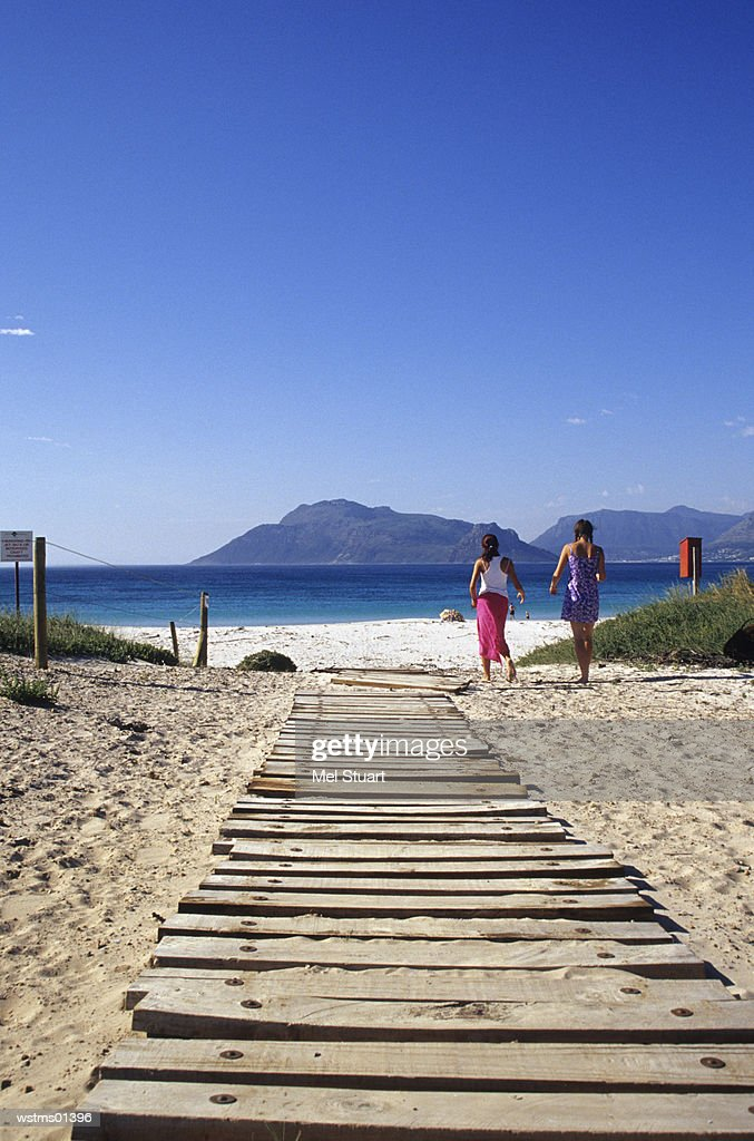 Two women walking towards beach, South Africa : Foto de stock