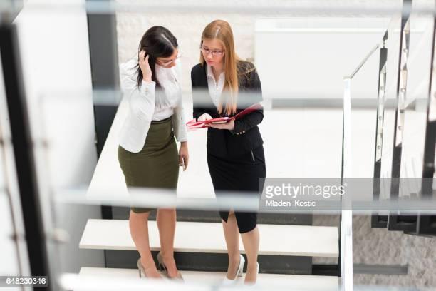 Zwei Frauen, die das Treppensteigen im Bürogebäude