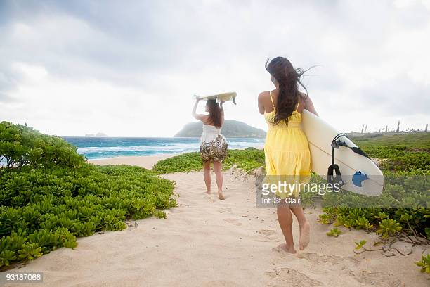 two women walking with surfboards toward ocean - kailua stock pictures, royalty-free photos & images