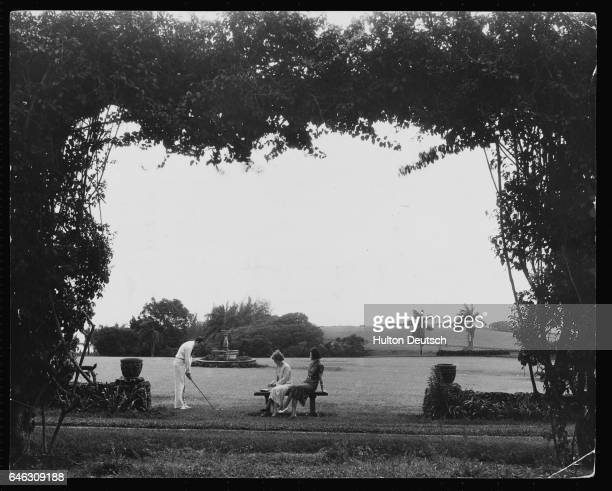Two women watch a man tee off at a golf course on Kauai
