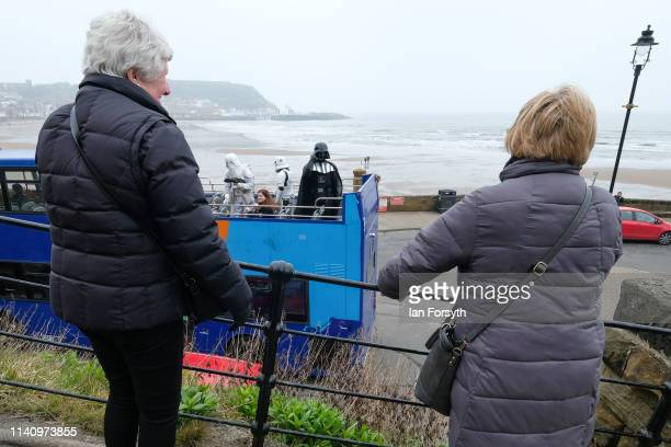Two women watch as Darth Vader rides an open top bus on the second day of the Scarborough Sci-Fi weekend held at the seafront Spa Complex on April...