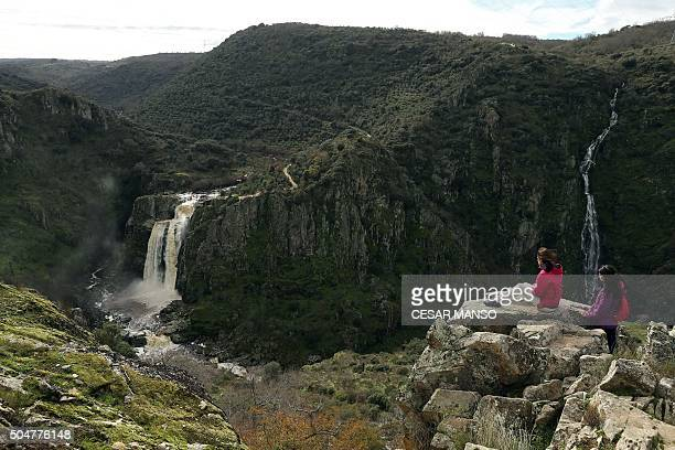 Two women watch El Pozo de los Humos waterfall on January 13 near Masueco in the province of Salamanca Heavy rains in recent days in the Natural Park...