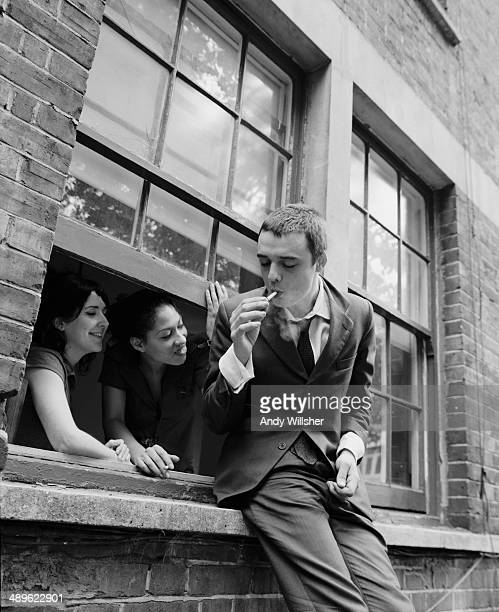 Two women watch from a window as English singer-songwriter and musician Pete Doherty, of The Libertines, lights a cigarette, circa 2003.