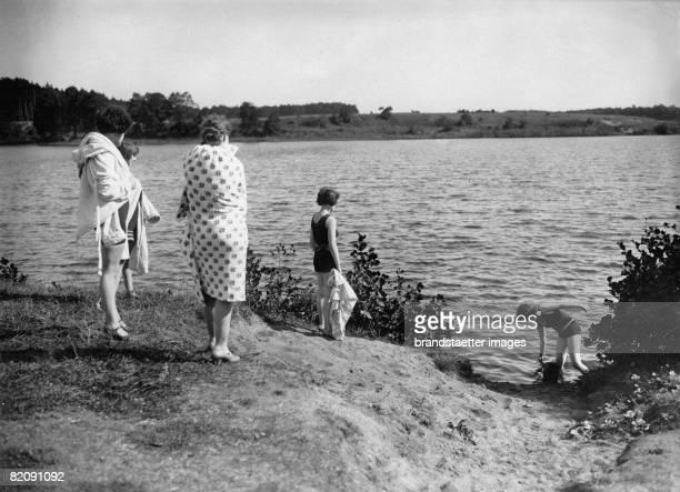 Two women watching girls bathing in a lake Photograph Around 1935 [Zwei Erwachsene beobachten zwei Mdchen beim Baden Photographie Um 1935]