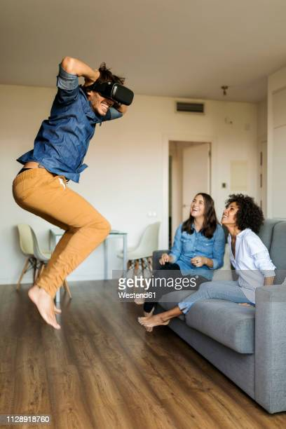 two women watching man with vr glasses jumping at home - último cuarto deportes fotografías e imágenes de stock