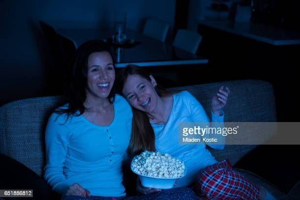 Two women watching tv together, comedy movie