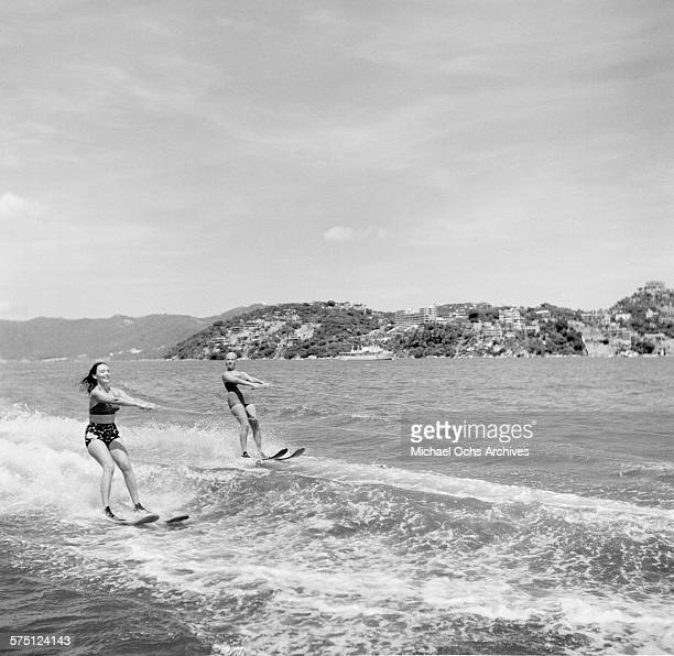 Two women water ski off the beach in Acapulco Mexico