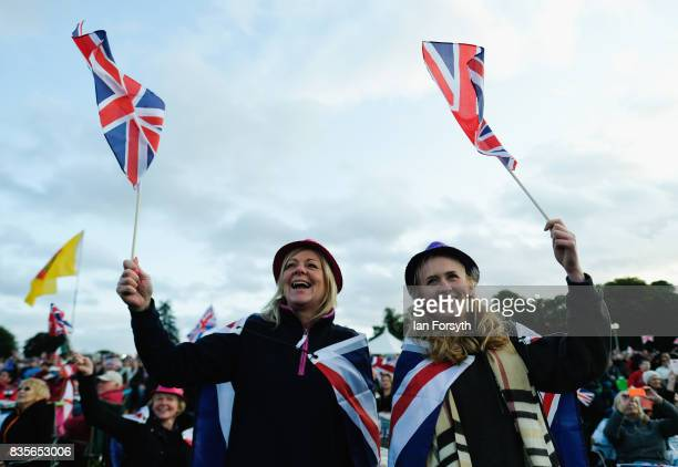Two women wave flags as they join thousands of spectators attending the annual Castle Howard Proms Spectacular concert held on the grounds of the...