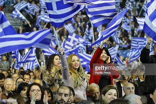 Two women wave Greek flags Néa Dimokratía the current main government party held their final election rally in Athens The only speaker was the party...