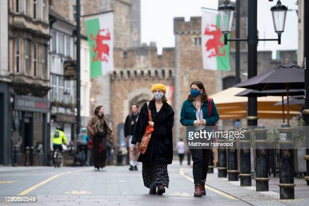 Two women wear face masks as they walk down St. Mary Street near Cardiff Castle on October 18, 2020 in Cardiff, Wales. The Welsh government is...