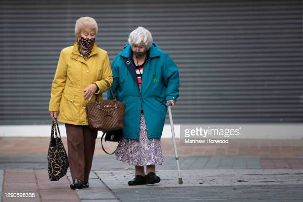Two women wear face masks as they walk through the town centre on November 07, 2020 in Merthyr Tydfil, Wales. The number of coronavirus patients in...