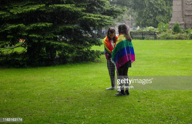 Two women wear pride flags as they stand in a heavy rain shower as thousands of people take to the streets to take part in the Newcastle Pride...
