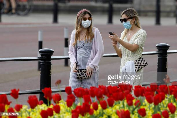 Two women wear protective face masks as they walk past the flowers outside Buckingham Palace in London on April 12 during the nationwide lockdown to...