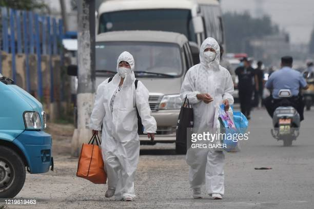 Two women wear protective suits as they walk on a street near the closed Xinfadi market in Beijing on June 13, 2020. - Eleven residential estates in...