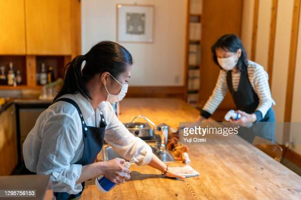 two women wearing a mask, carefully wipe a counter  and enthusiastically disinfect in preparation for opening - catering building stock pictures, royalty-free photos & images
